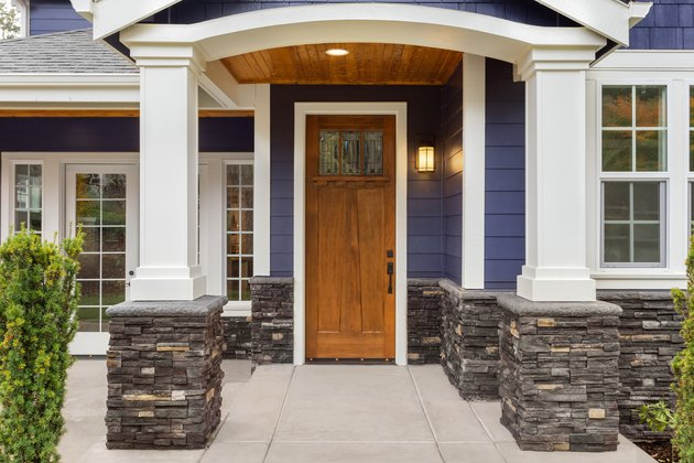new luxury home exterior detail: patio and front door with arch and columns. Stonework graces the bottom of the columns and house while white columns and archway provide a stately welcome