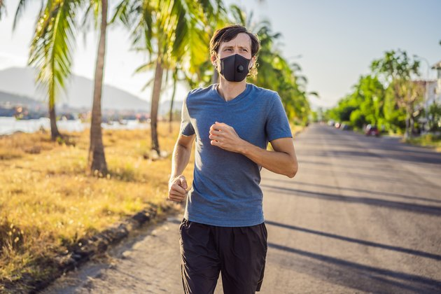 Runner wearing medical mask, Coronavirus pandemic Covid-19. Sport, Active life in quarantine surgical sterilizing face mask protection. Outdoor run on athletics track in Corona Outbreak. Keep your shape during quarantine, pandemic.