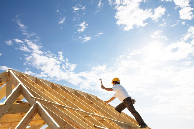 roofer worker builder working on roof structure at construction site