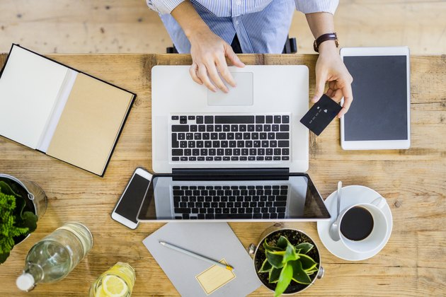 Top view of woman at wooden desk with credit card and laptop