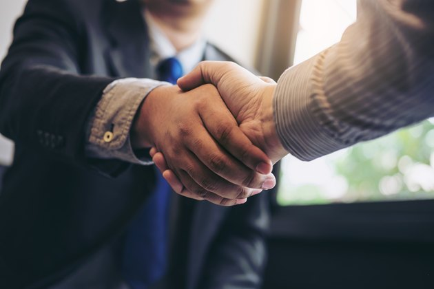 Two business men shaking hands during a meeting to sign agreement and become a business partner, enterprises, companies, confident, success dealing, contract between their firms