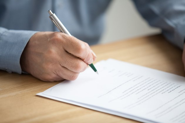 Male hand signing document, senior man putting signature on paper
