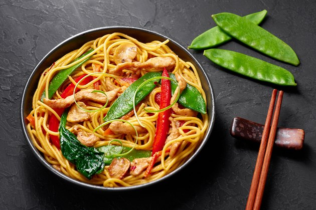 Chicken Lo Mein in black bowl at dark slate background. Lo Mein is Chinese cuisine dish with chicken meat, egg noodles, vegetables and sauces. Chinese Food. Stir Fried Noodles.