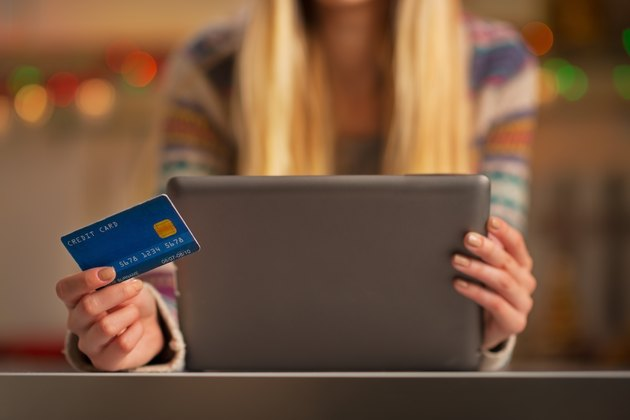 How Do Teenagers Build Credit?               closeup on teenager girl with credit card using tablet pc