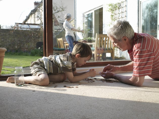 Grandfather and grandson (5-7) counting coins on floor