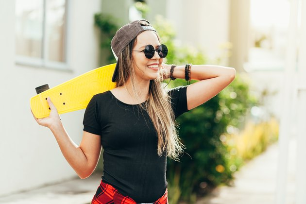 Portrait of smiling young female skateboarder with her skateboard outdoors