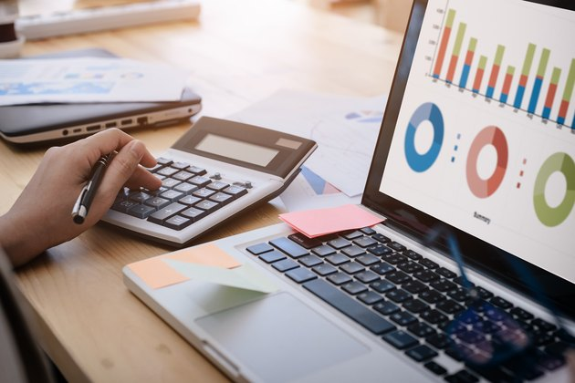 business woman uses a calculator to calculate the company's performance figures, graphs the monthly graphs for the meeting.