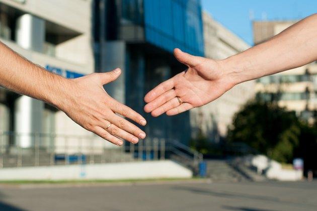 men shaking hands on building background