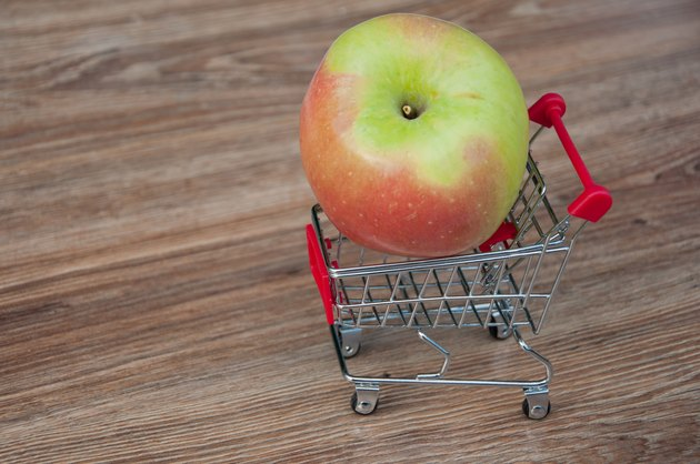 Big apple laying in shopping cart. Wooden background