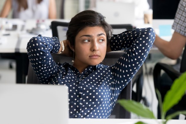 Thoughtful Indian female employee leaning back in chair at workplace