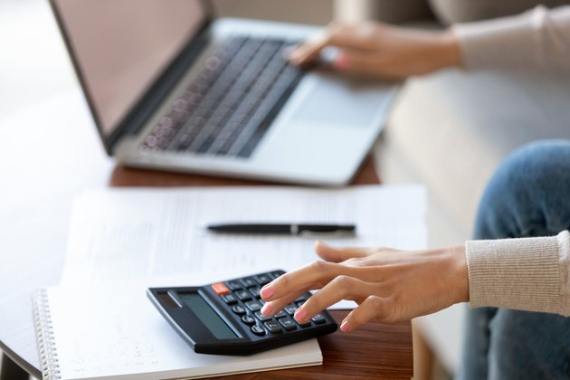 Businesswoman using calculator and laptop for budget cost management, closeup