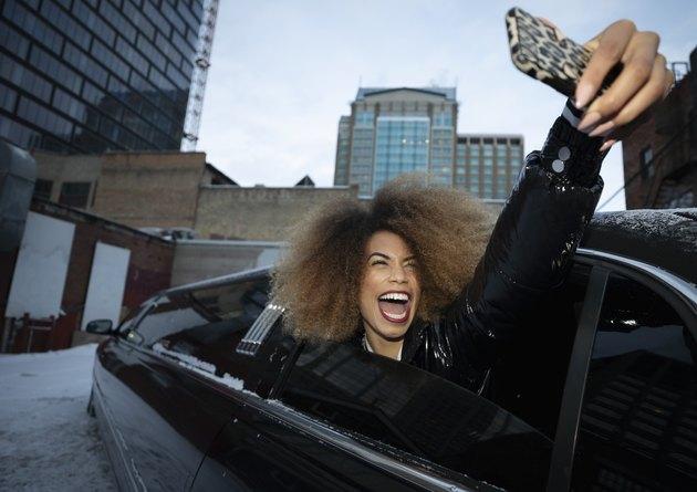 Exuberant young woman taking selfie in limousine window