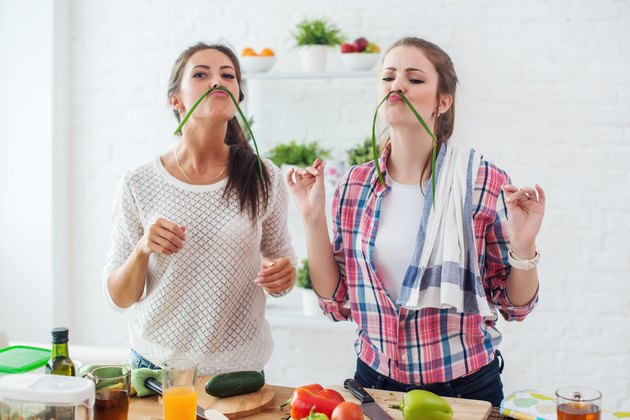 Women preparing healthy food playing with vegetables in kitchen having