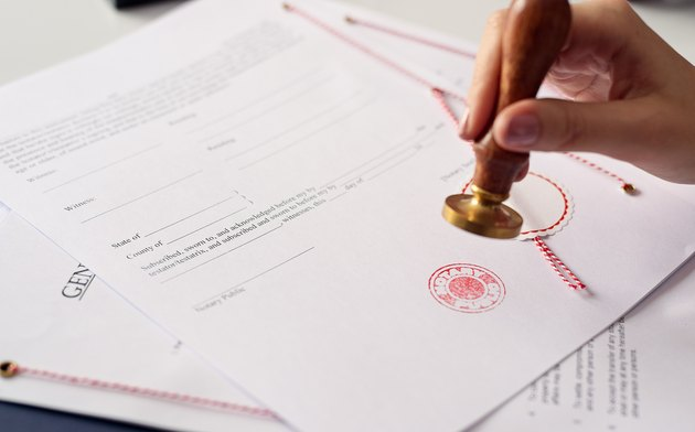How to Cosign an Auto Loan if the Cosigner Lives out of StateClose up on woman's notary public hand  stamping the document