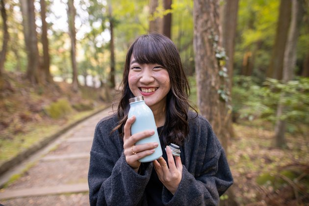Young woman holding stainless bottle in forest
