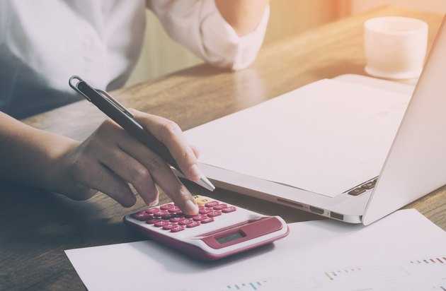 Young female calculates cost on desk at home office