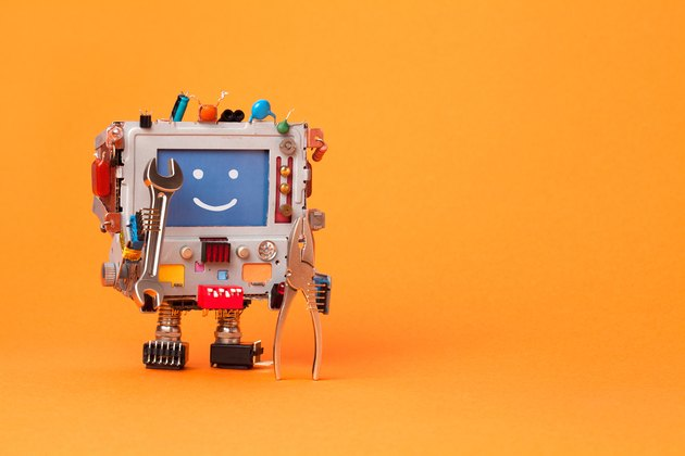 Fixing computer concept. Robotic electrician with hand wrenches for repair. Colorful display toy, smile message blue monitor. Service system communication concept. Orange background, copy space