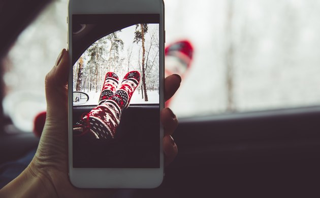Girl makes a photo on her smartphone in the forest. The concept of the winter vacation relax.