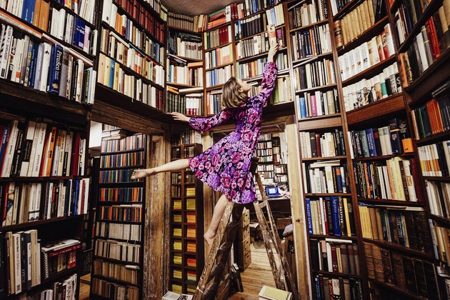 Carefree woman on ladder reaching for book in library