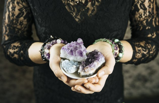 Healer woman holding different crystal clusters( amethyst, celestite) in palms hands. Close up view, using working with crystals concept.