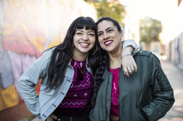 Two Young Latina Women Leaning Together, Smiling and Happy