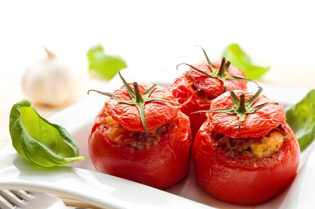 Baked stuffed tomatoes served with fresh basil