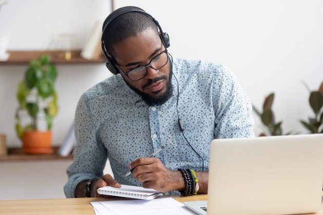 Focused african businessman in headphones writing notes watching webinar