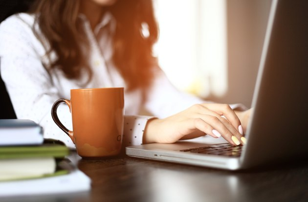 Closeup of a female hands busy typing on a laptop