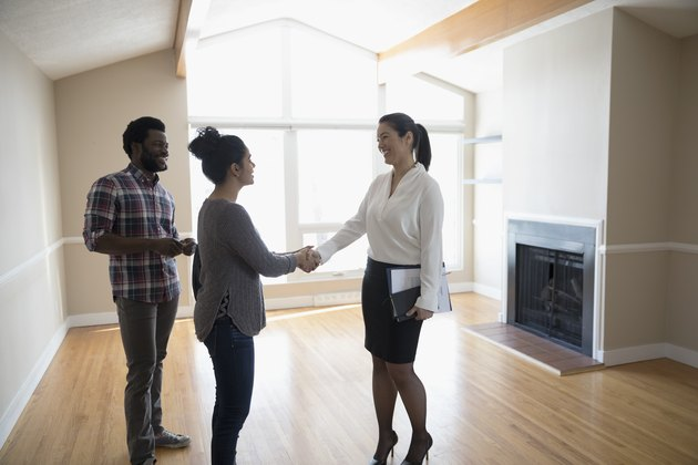 Young couple buying new house, handshaking with realtor in agreement