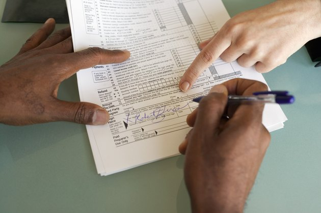 How to Fill Out and File IRS Form 1041                 Man signing financial paperwork