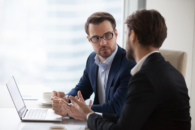 Two young businessmen discuss or plan project in office