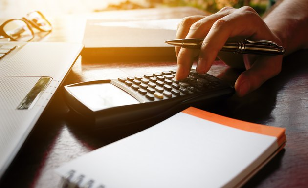 Businessman hand calculate bout cost with laptop for search data.