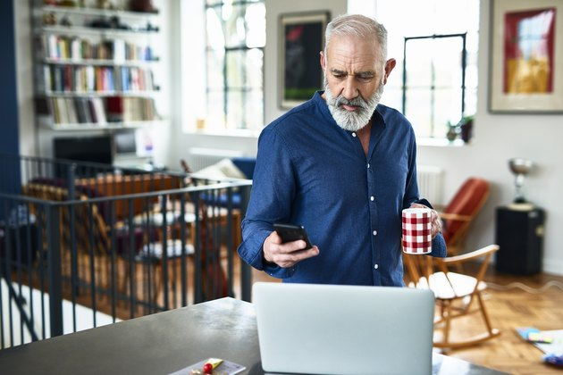 Senior creative professional remote working and checking phone at home