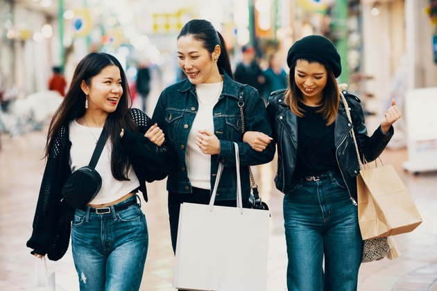 Three mid adult women with bags shopping in the city