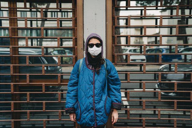 Portrait of a young woman with a protective mask in front of closed stores