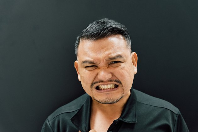 Portrait Of Angry Mature Man Against Black Background