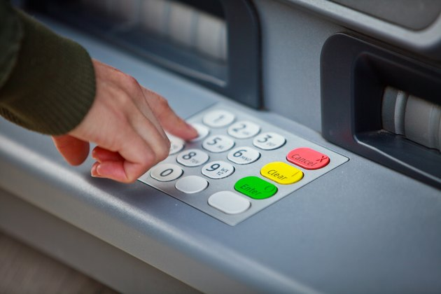 Cropped Hand Of Man Using Atm