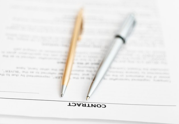 Can You Trade in a Vehicle Without a Signature From the Primary?sales contract and two pens close up