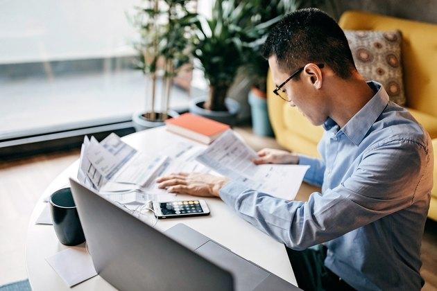 Japanese man calculating financial bills at home