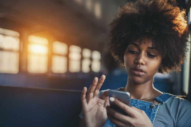 Cute mixed girl in train chatting via smartphone