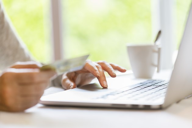 Woman indoors using credit card and laptop. Shopping online.