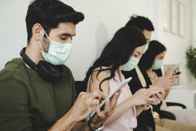 group of business people wearing protective face mask using digital mobile phone connection internet in meeting room at office, network technology, social media marketing, business startup concept