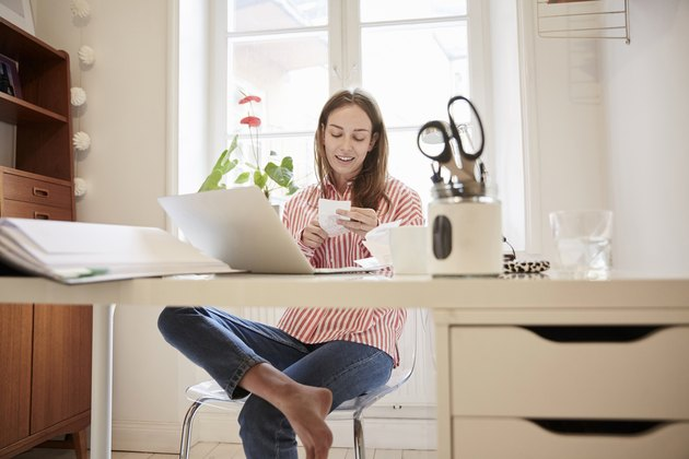 Full length of young woman examining financial bill while working from home