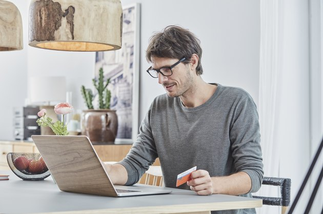 Man holding a card using laptop on table at home