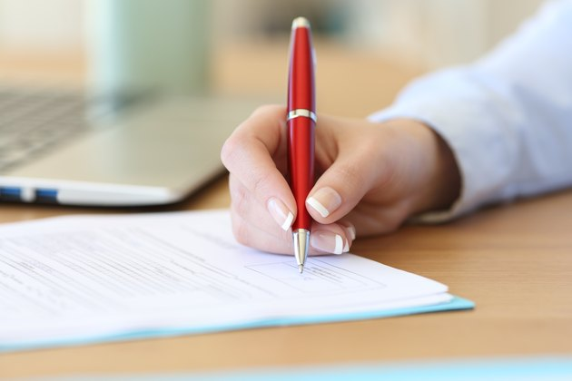 Businesswoman hand signing a contract on a desk