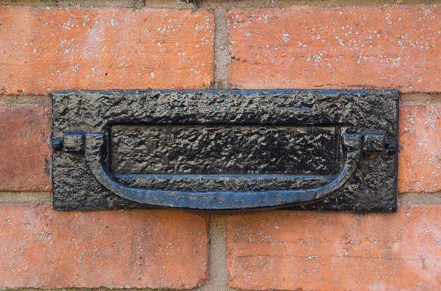 How Much Does a Brick Mailbox Cost? Black metal letter box on a red brick wall.