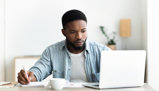 Unemployed man using laptop searching for vacancies online in internet