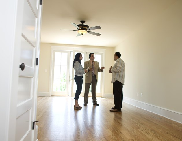 "What Does ""Owner Will Carry Note"" Mean?Couple with realtor looking at new home"
