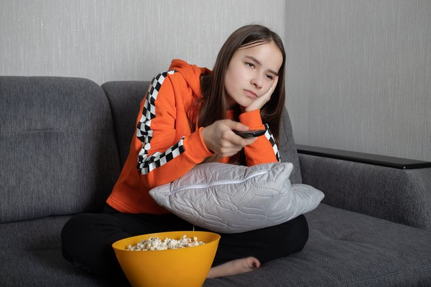 Young woman watching an uninteresting TV show