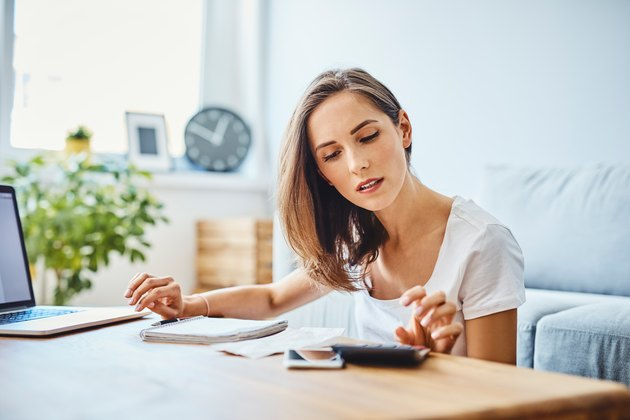 Young woman preparing home budget, using laptop and calculator